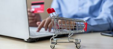 Close up mini cart, Asian businessman holding credit card and using laptop for online shopping while making orders. internet, stock photos