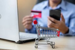 Close up mini cart, Asian businessman holding credit card using laptop and smart phone for online shopping while making orders. stock photos
