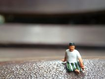 Mini figure toy old man sit at scratch wooden chair, with copy or negative space for text placement area. Close Up Mini figure toy old man sit at scratch wooden royalty free stock image