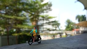 Close up Mini Figure Woman toys bicycling at River Side Path Way with negative or copy space for text area placement. Mini Figure Woman toys bicycling at River royalty free stock photo
