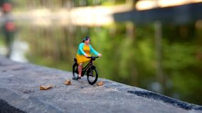 Close up Mini Figure Woman toys bicycling at River Side Path Way with negative or copy space for text area placement. Mini Figure Woman toys bicycling at River stock images