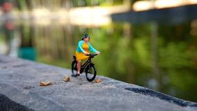 Close up Mini Figure Woman toys bicycling at River Side Path Way with negative or copy space for text area placement. Mini Figure Woman toys bicycling at River royalty free stock image