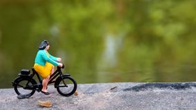 Close up Mini Figure Woman toys bicycling at River Side Path Way with negative or copy space for text area placement. Mini Figure Woman toys bicycling at River stock photos