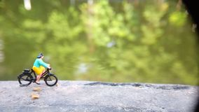 Close up Mini Figure Woman toys bicycling at River Side Path Way with negative or copy space for text area placement. Mini Figure Woman toys bicycling at River royalty free stock photography