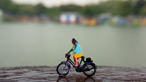 Close up Mini Figure Woman toys bicycling at River Side Path Way with negative or copy space for text area placement. Mini Figure Woman toys bicycling at River royalty free stock photos