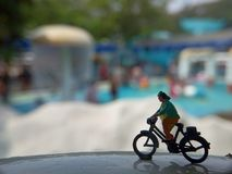 Close up Mini Figure Woman toys bicycling at Water Park White Horizontal Pool with negative or copy space for text area placement. Mini Figure Woman toys royalty free stock images
