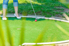 Close-up Mini Golf hole with bat and ball. Close-up of a miniature golf course with feet racket red ball Royalty Free Stock Photo