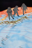 Close up of miniature figurines of astronomers on globe Stock Photo