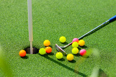Close-up of miniature golf hole with bat and ball.  Royalty Free Stock Photo