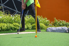Close-up of miniature golf hole with bat and ball. Stock Photo