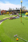 Close-up of miniature golf hole with bat and ball. Close-up of miniature golf hole with bat and ball Royalty Free Stock Image