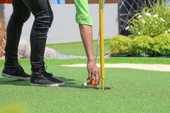 Close-up of miniature golf hole with bat and ball. Close-up of miniature golf hole with bat and ball Royalty Free Stock Photography