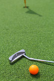 Close-up of miniature golf hole with bat and ball. Close-up of miniature golf hole with bat and ball Stock Images