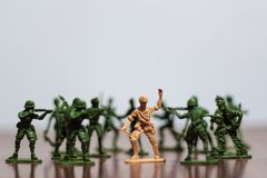 Close-up of miniature a group of plastic toys soldiers at war. stock photo