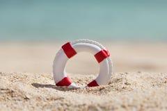 Close-up of miniature lifebuoy. On Sandy Beach Royalty Free Stock Image