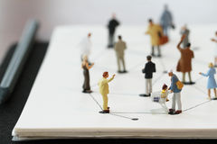 close up of miniature people with social network diagram on open Stock Images