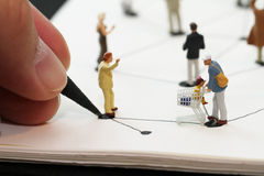 close up of miniature people with social network diagram on open Royalty Free Stock Photos