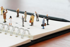 close up of miniature people with social network diagram on open Royalty Free Stock Photography