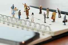 close up of miniature people with social network diagram on open Stock Image