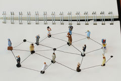 Close up of miniature people with social network diagram. On open notebook on wooden desk as social media concept royalty free stock photo