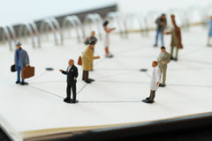 Close up of miniature people with social network diagram. On open notebook on wooden desk as social media concept royalty free stock image