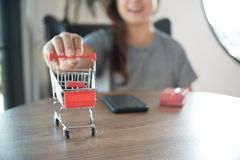 Close up of miniature shopping cart /trolley toy figure. smart phone and red gift box on table for shopping and e-commerce concept stock photography
