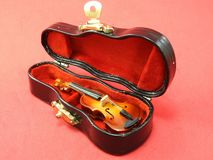 Close-up of a miniature violin inside its black case, on a pink surface. stock images