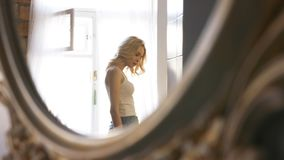 Close-up of mirror reflection of young blond woman in white t-shirt and blue jeans walking near a window in her stock image