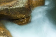 Close-up of misty water and orange granite, New Hampshire. Royalty Free Stock Images