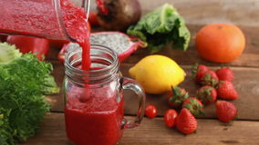Close up of mix fruit and vegetable smoothie pouring into glass. stock footage
