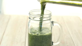 Close up of mix green fruit and vegetable smoothie pouring into glass. stock video