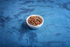 Close up of mix of peppers in a pot against a blue stone background. spice royalty free stock photo