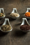 Close up of mixed grains in white spoons on wood Royalty Free Stock Image