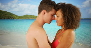 Close up of mixed race couple cuddling together on tropical beach. Royalty Free Stock Image