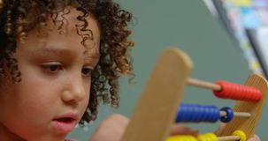 Close-up of mixed-race schoolgirl learning mathematics with abacus in a classroom at school 4k. Close-up of mixed-race schoolgirl learning mathematics with stock footage