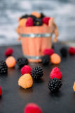 Close up of mixed red, black, yellow raspberries on  table with basket  backround. Stock Photo