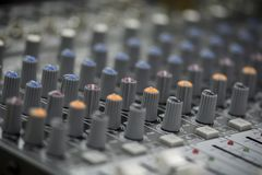 Close up of a mixing console with sliders and buttons. stock images