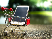 Close up the mobile phone in shopping cart, business in eCommerce concept.  Royalty Free Stock Images