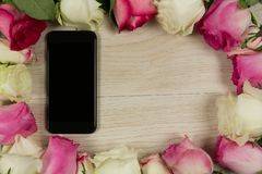 Mobile phone surrounded with rose flower. Close-up of mobile phone surrounded with rose flower stock photos
