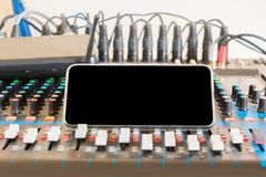 Close up mobile telephone on audio mixer controller in control room.  stock photo