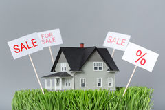 Close up of model house for sale. On green grass, grey background. Concept of real estate and property Royalty Free Stock Photo