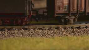 Close up model of toy locomotive moving on railroad.