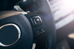 Audio control buttons on the steering wheel of a modern car. Close up Modern black steering wheel with multifunction buttons Integrated stereo controls pushes royalty free stock photo