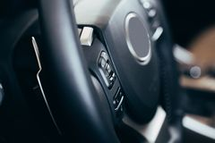Audio control buttons on the steering wheel of a modern car. Close up Modern black steering wheel with multifunction buttons Integrated stereo controls pushes royalty free stock photography