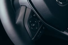 Audio control buttons on the steering wheel of a modern car. Close up Modern black steering wheel with multifunction buttons Integrated stereo controls pushes stock images