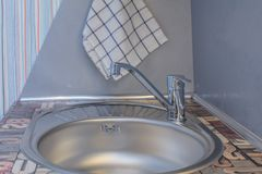 Faucet in kitchen. Close up of modern faucet and ceramic sink in kitchen stock photo