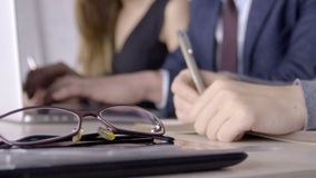 Close up of modern glasses which are lying on the office table. Two colleagues are working at the background sitting at the desk with laptop on. Male and stock footage