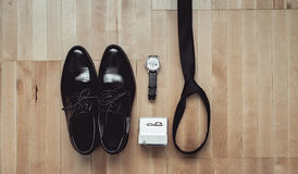 Close up of modern groom accessories. wedding rings, black necktie, leather shoes and watch. On the wooden floor. Selective focus Royalty Free Stock Image