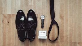 Close up of modern groom accessories. wedding rings, black necktie, leather shoes and watch. On the wooden floor. Selective focus Royalty Free Stock Images