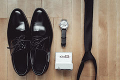 Close up of modern groom accessories. wedding rings, black necktie, leather shoes and watch. On the wooden floor. Selective focus Stock Photos